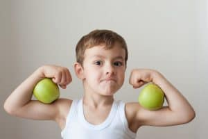 Boy with green apples as biceps
